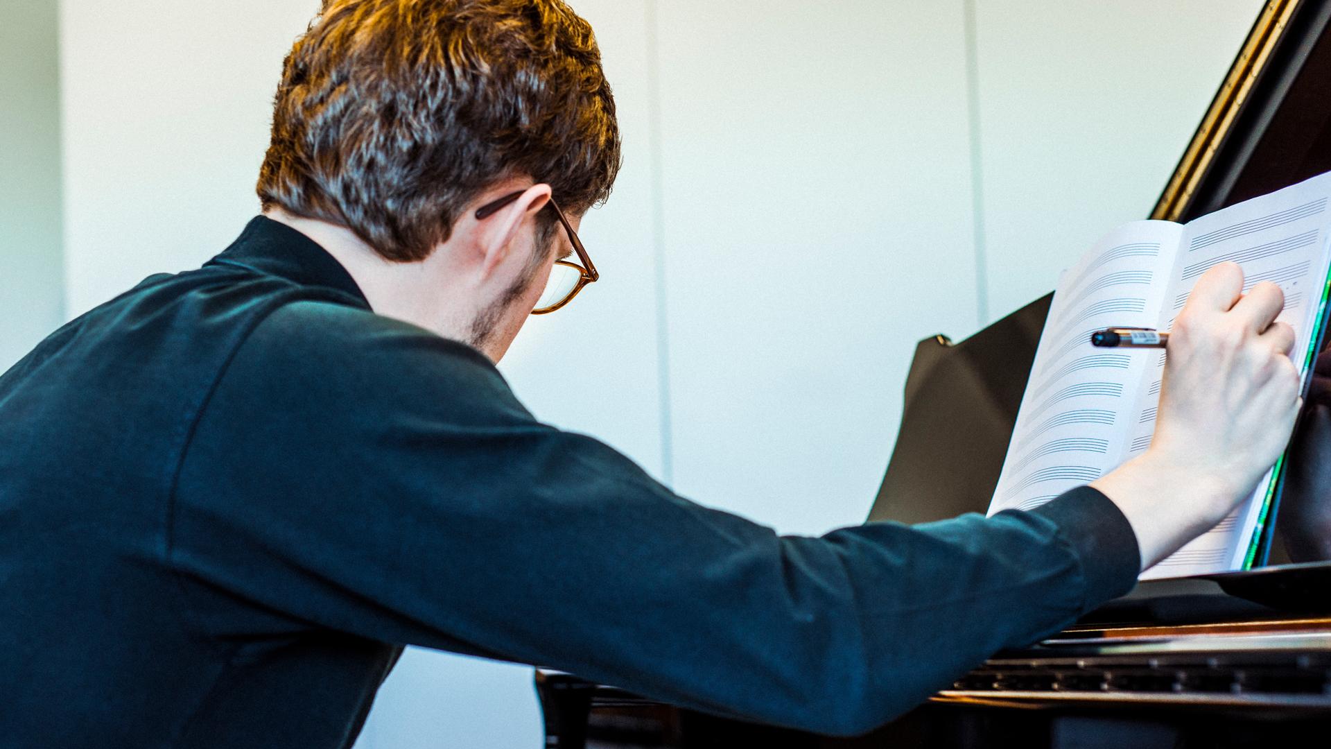 Mies säveltää pianon ääressä