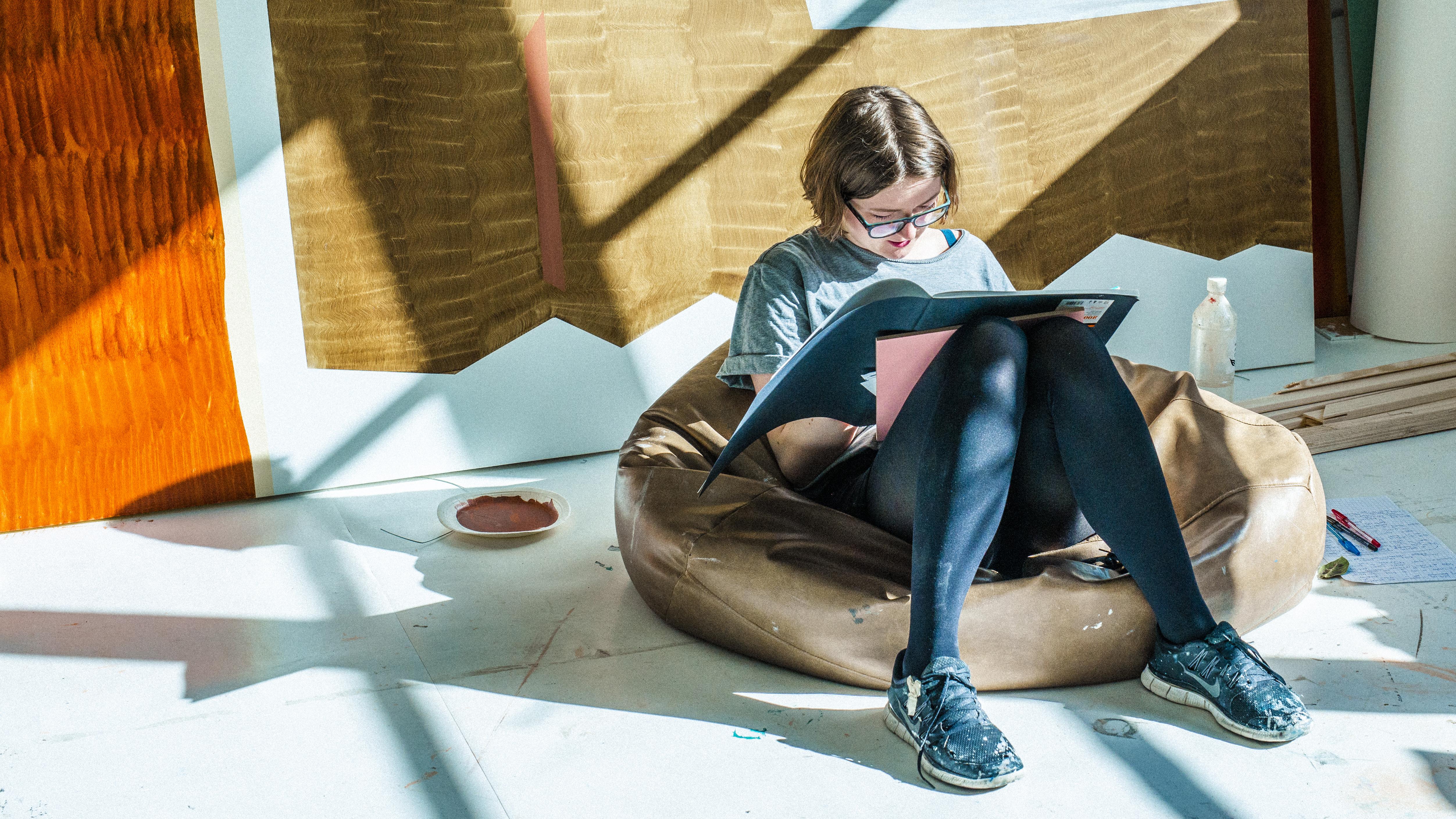 Nainen lukee kirjaa säkkituolissa