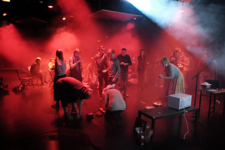 Opiskelijoita lavalla esiintymässä punaisessa valossa