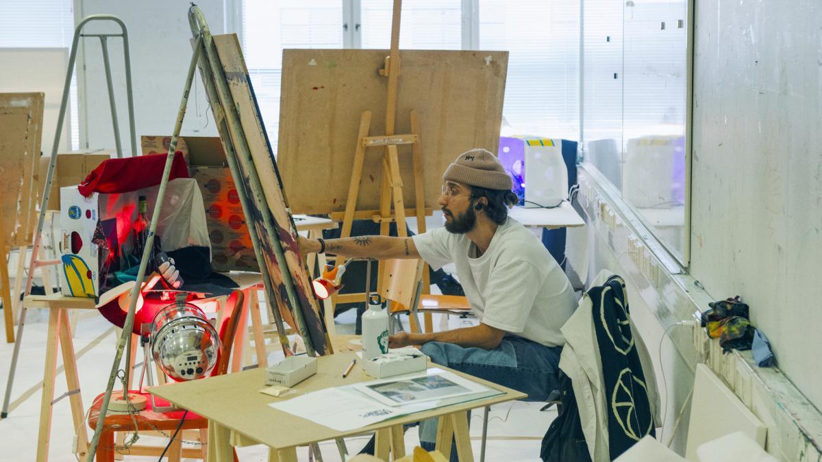 Opiskelija maalaa taulua maalausluokassa