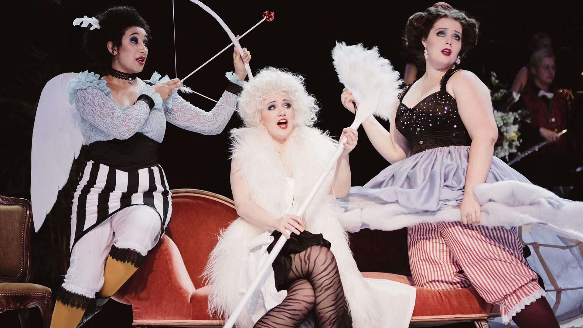 Kolme opiskelijaa esittää oopperaa lavalla.