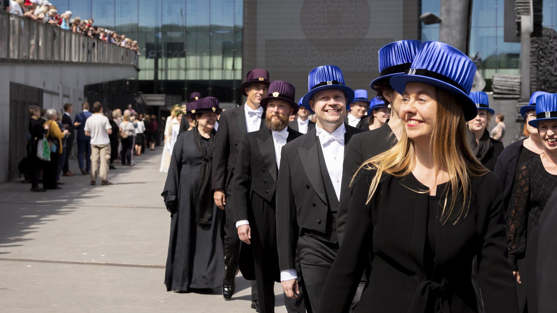 Musiikintohtoreita promootiokulkueessa sinisissä musiikintohtorin hatuissaan Musiikkitalon ulkopuolella.