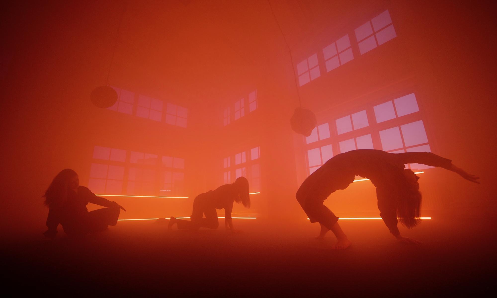 Kolme tanssijaa tanssivat hämärästi valaistussa tilassa.