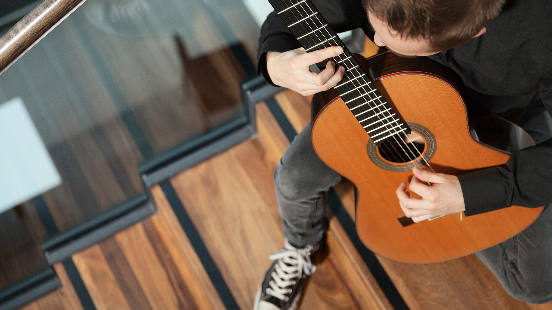 Mies soittaa portailla kitaraa