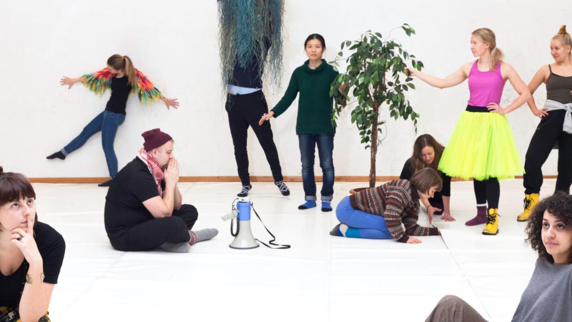 Ihmisiä poseeramassa vaaleassa huoneessa erilaisten esineiden kanssa.