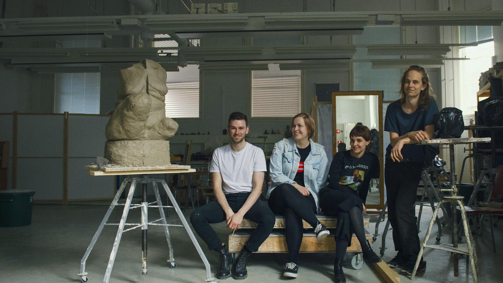 Joukko opiskelijoita poseeraa kuvataideluokassa