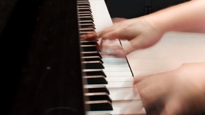Opiskelijan kädet soittamassa pianoa