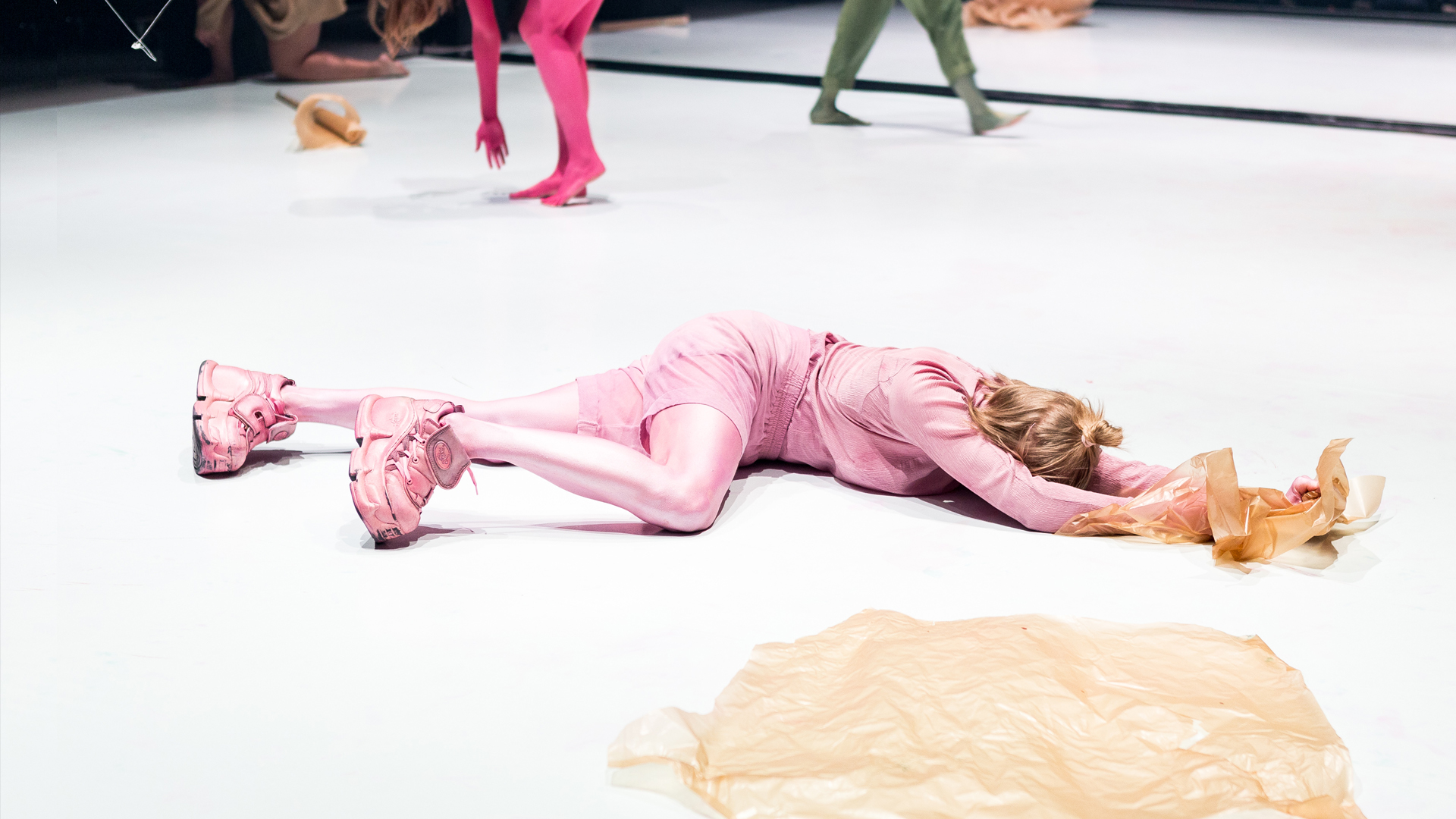 Vaaleanpunaiseksi maalattu henkilö makaa kasvot alaspäin lattialla.