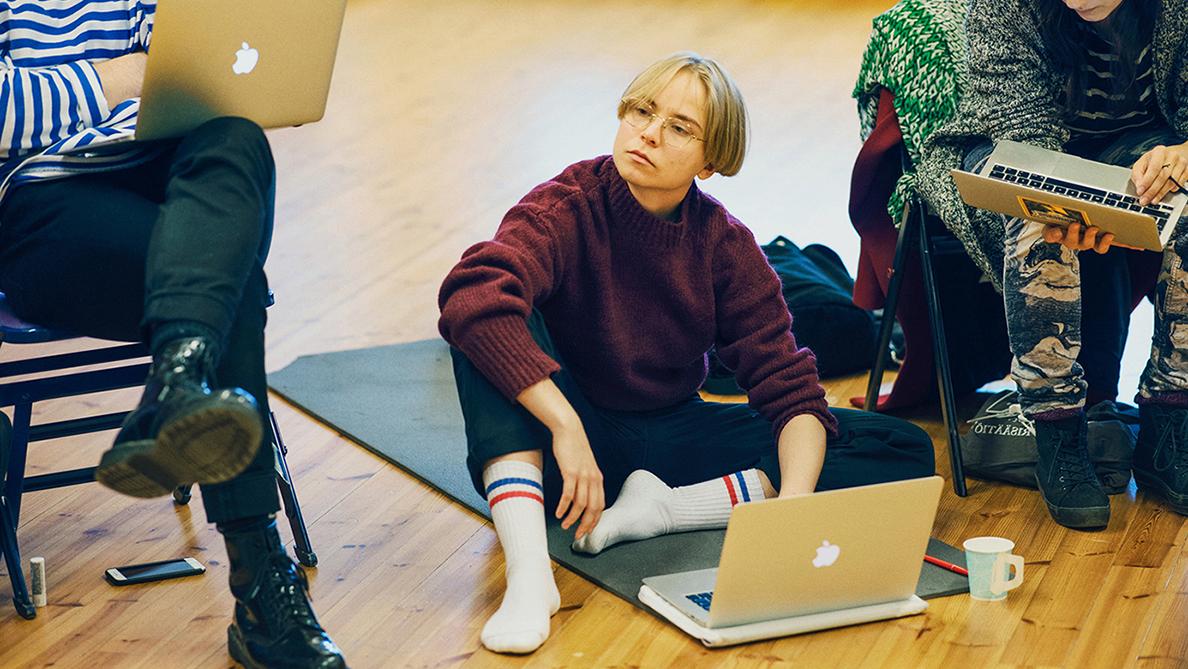 Opiskelija istuu lattialla tietokoneen kanssa