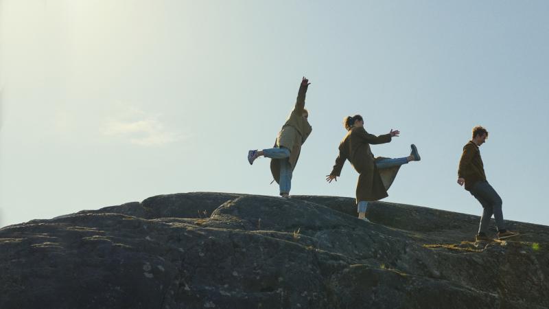 Kolme henkilöä kävelevät kallioilla.