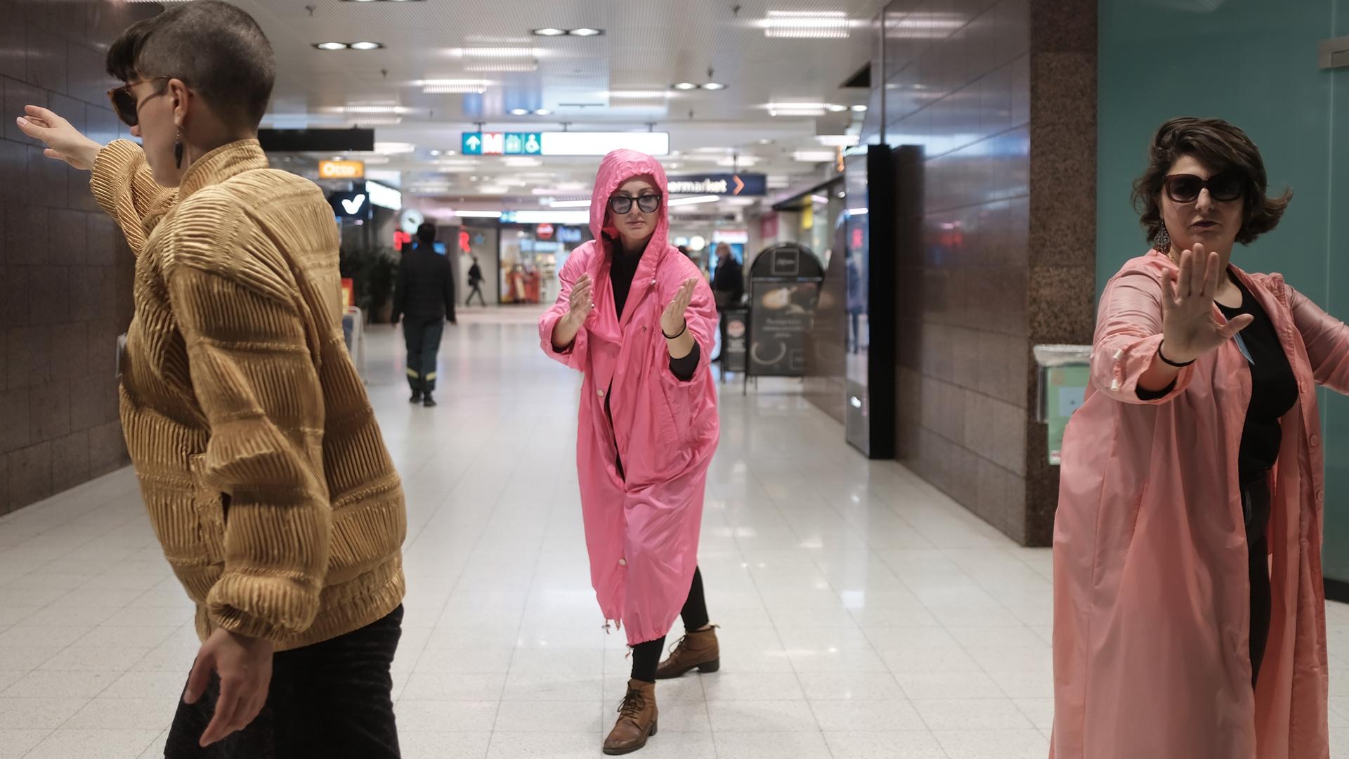 Kolme henkilöä seisoo metroasemalla eri asennoissa. Kaksi heistä katsoo kohti kameraa.