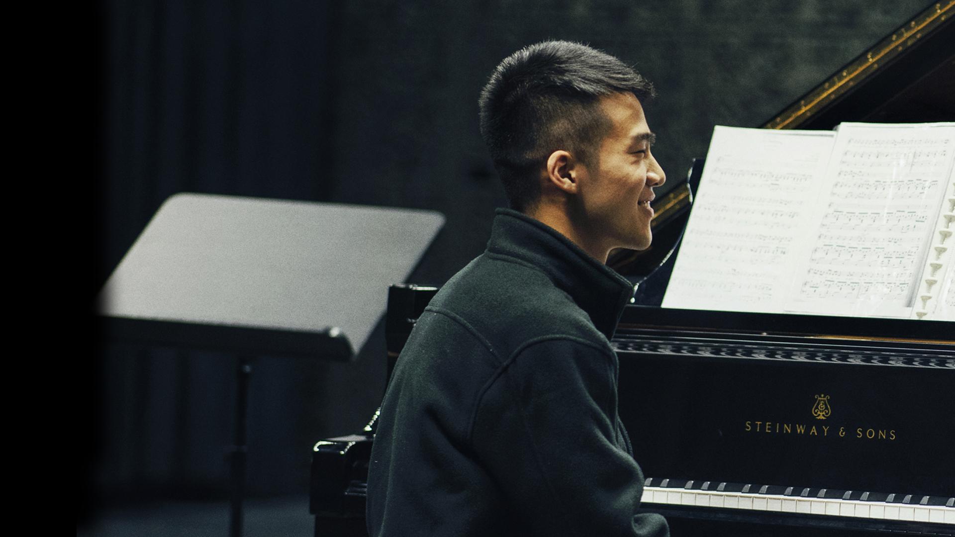 Mies hymyilee pianon ääressä