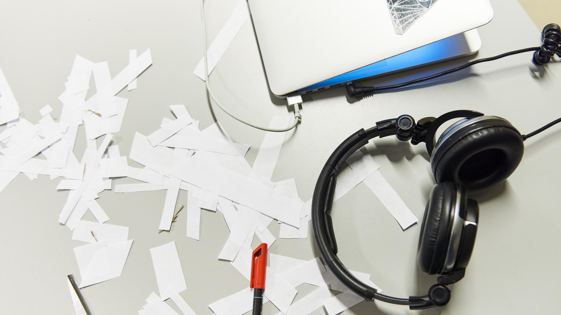 Tietokone, kuulokkeet ja paperisilppua pöydällä