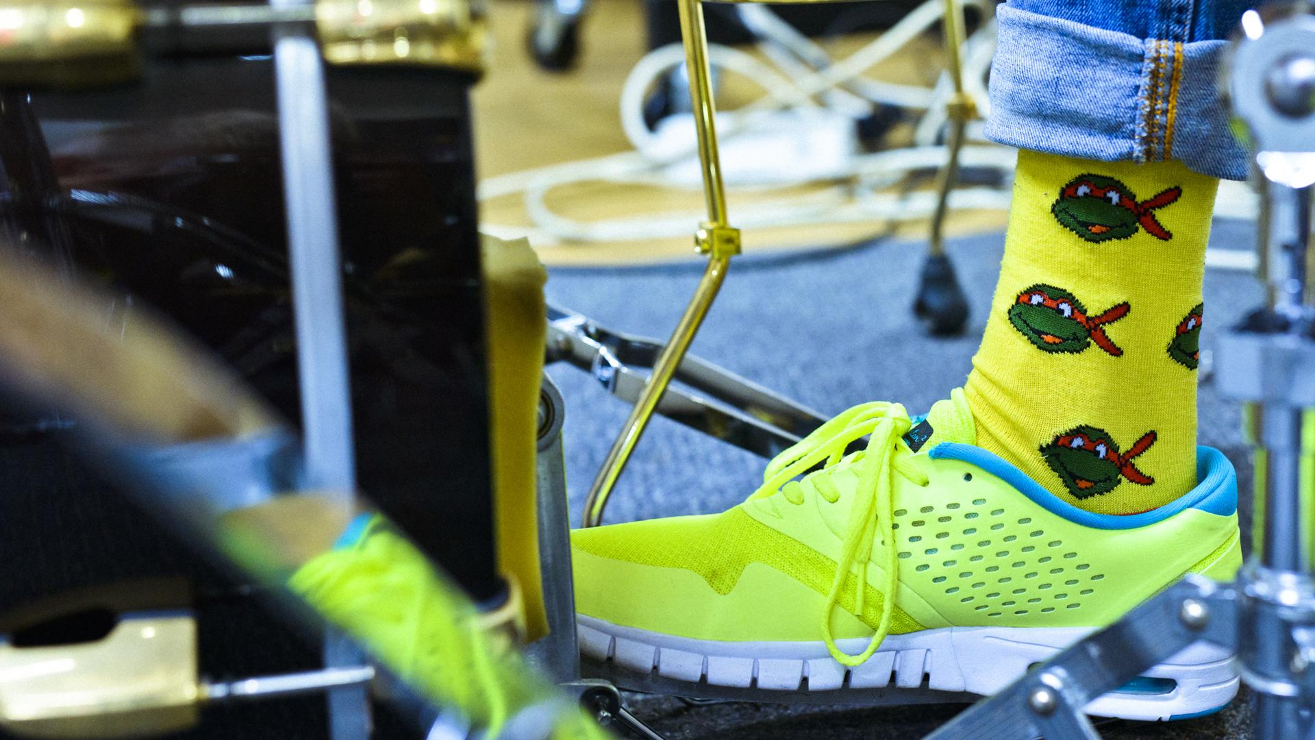 Jalka, jossa kirkas lenkkari ja värikäs sukka rumpujen keskellä.