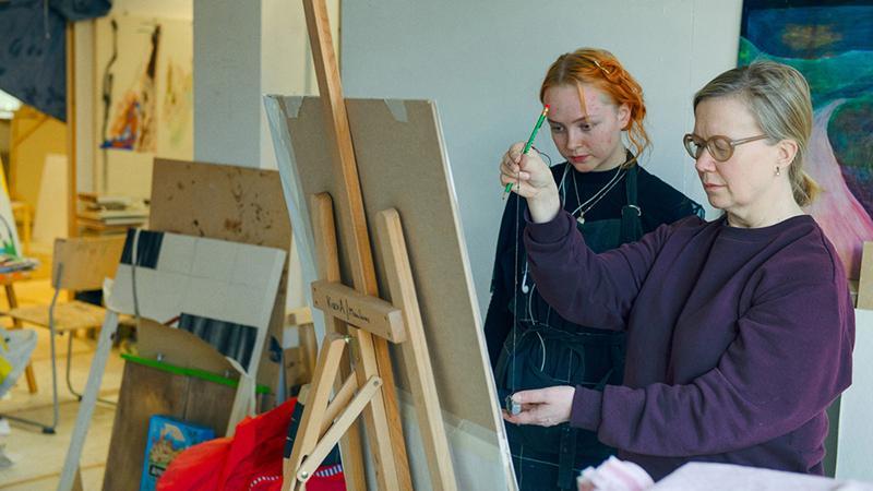Maalauksen opettaja ohjaa opiskelijan työtä maalaustelineen ääressä