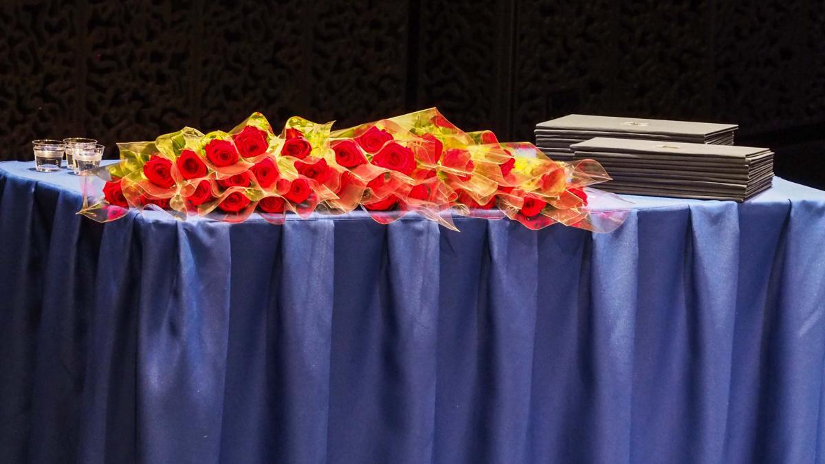 Ruusuja ja tutukintotodistusvihkoja pöydällä