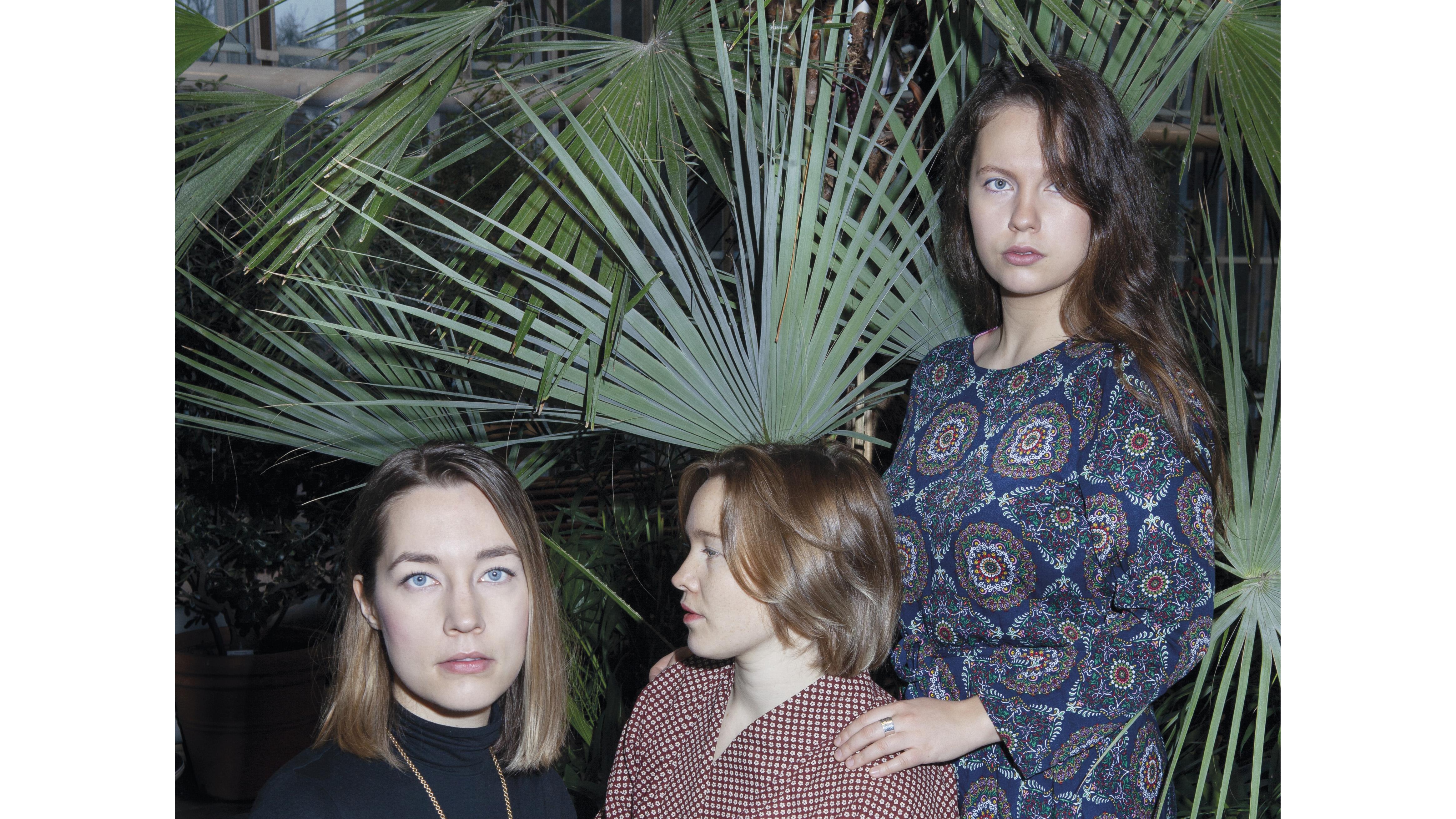 Kolme naista viherkasvin edessä
