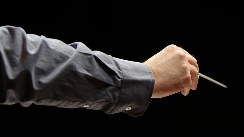 Käsi pitelee tahtipuikkoa