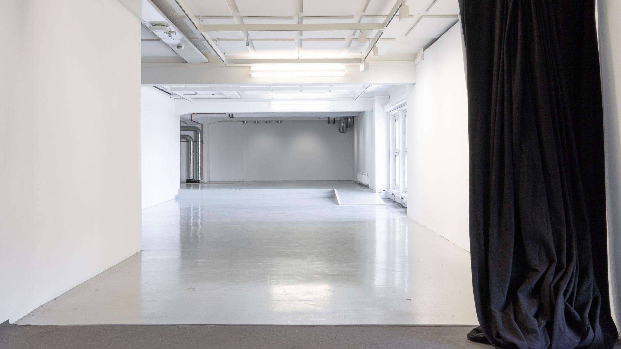 Tyhjä galleriatila, sivulla musta verho