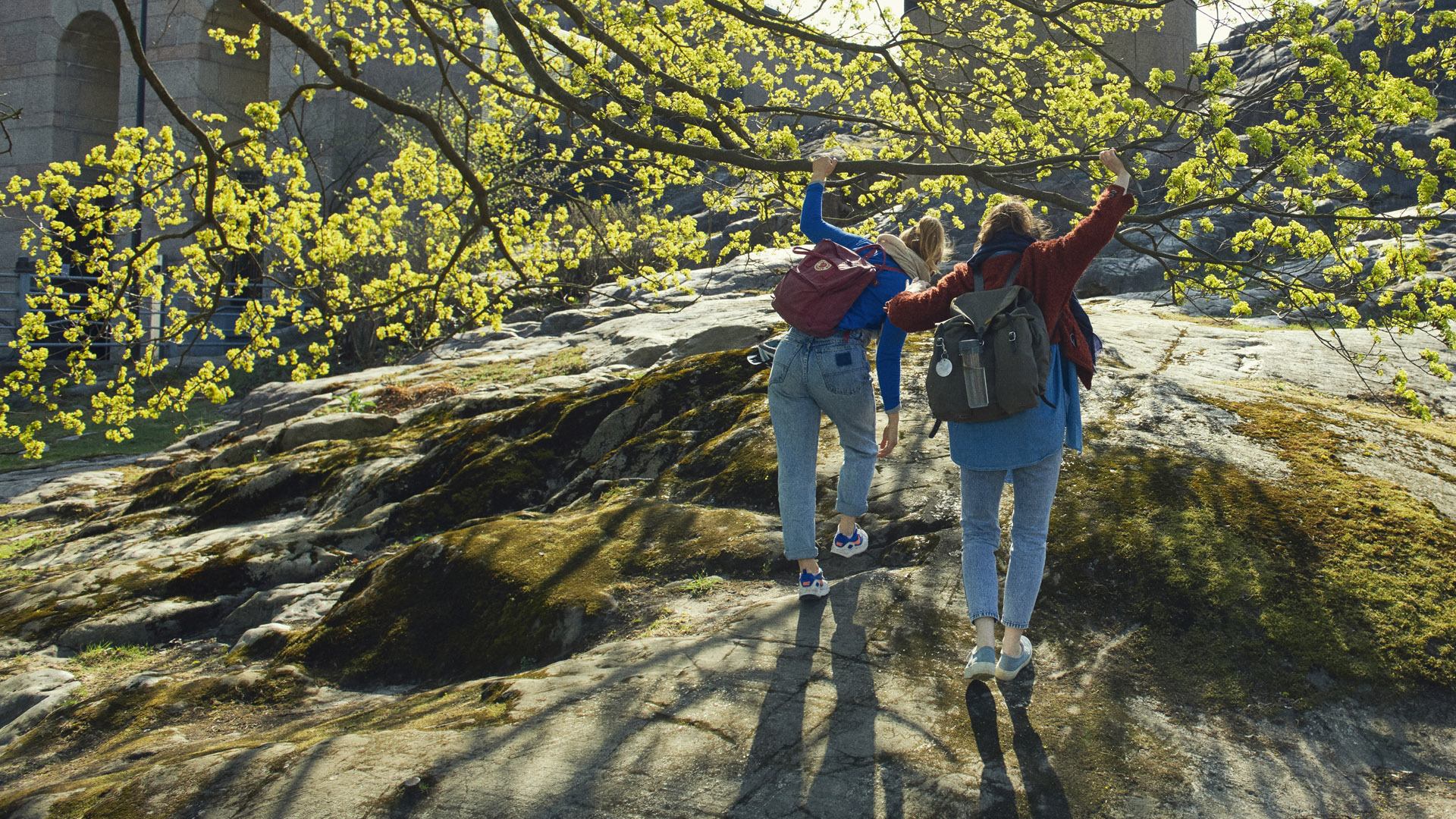 Kaksi reppuselkäistä ihmistä kiipeämässä kalliolla.