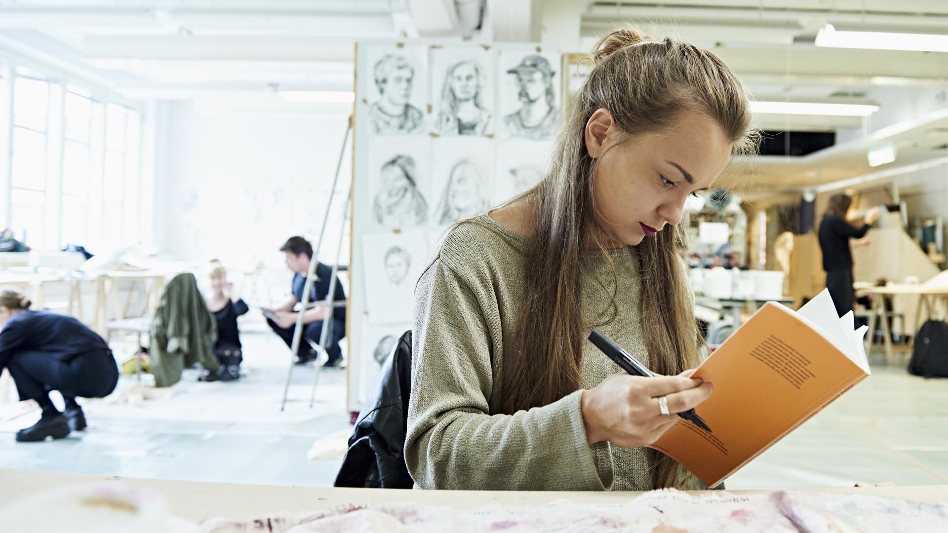 Opiskelija selaa kirjaa, taustalla piirustusluokka