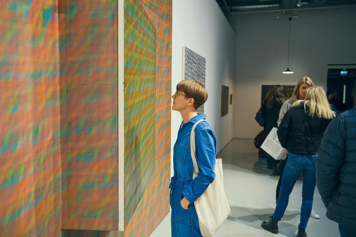 Henkilö katsoo teosta taidenäyttelyssä. Kuva: Veikko Kähkönen