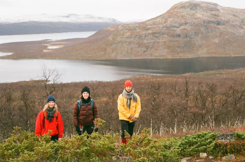 Kolme opiskelijaa kävelee kohti kameraa Lapin luonnossa.