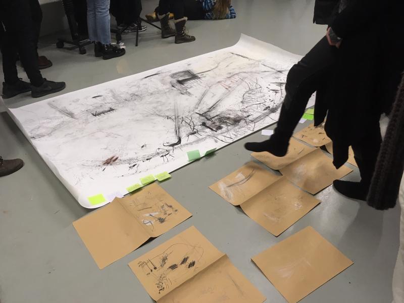 Ihmiset tutkivat piirroksia lattialla Kuvan tutkimuspäivillä.