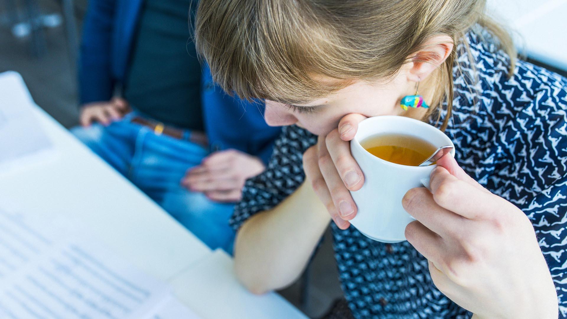 Nainen teekupin kanssa katselee paperia pöydän äärellä.