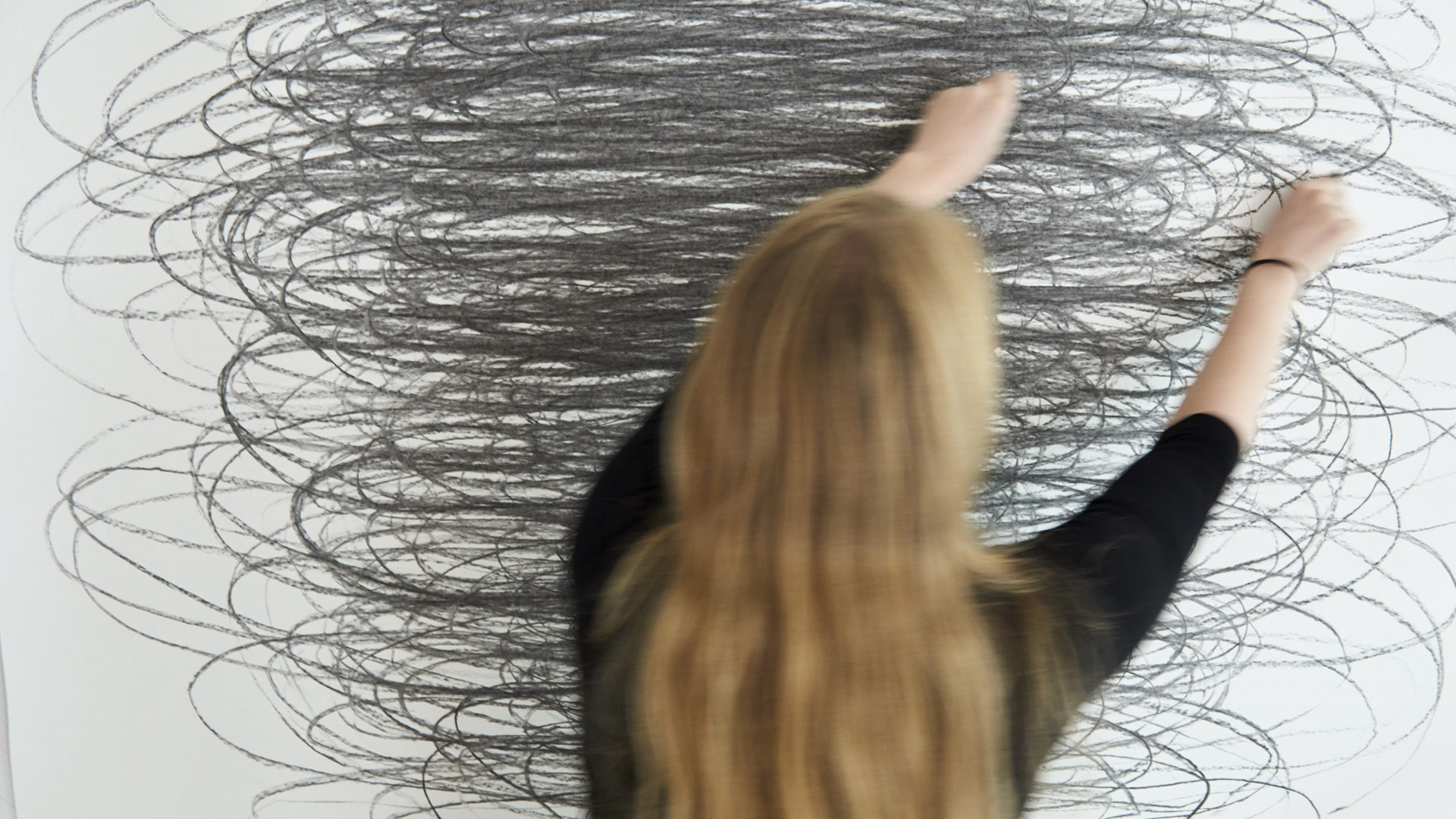 Opiskelija piirtää lyijykynällä kuvioita seinällä olevalle valkoiselle pohjalle,.