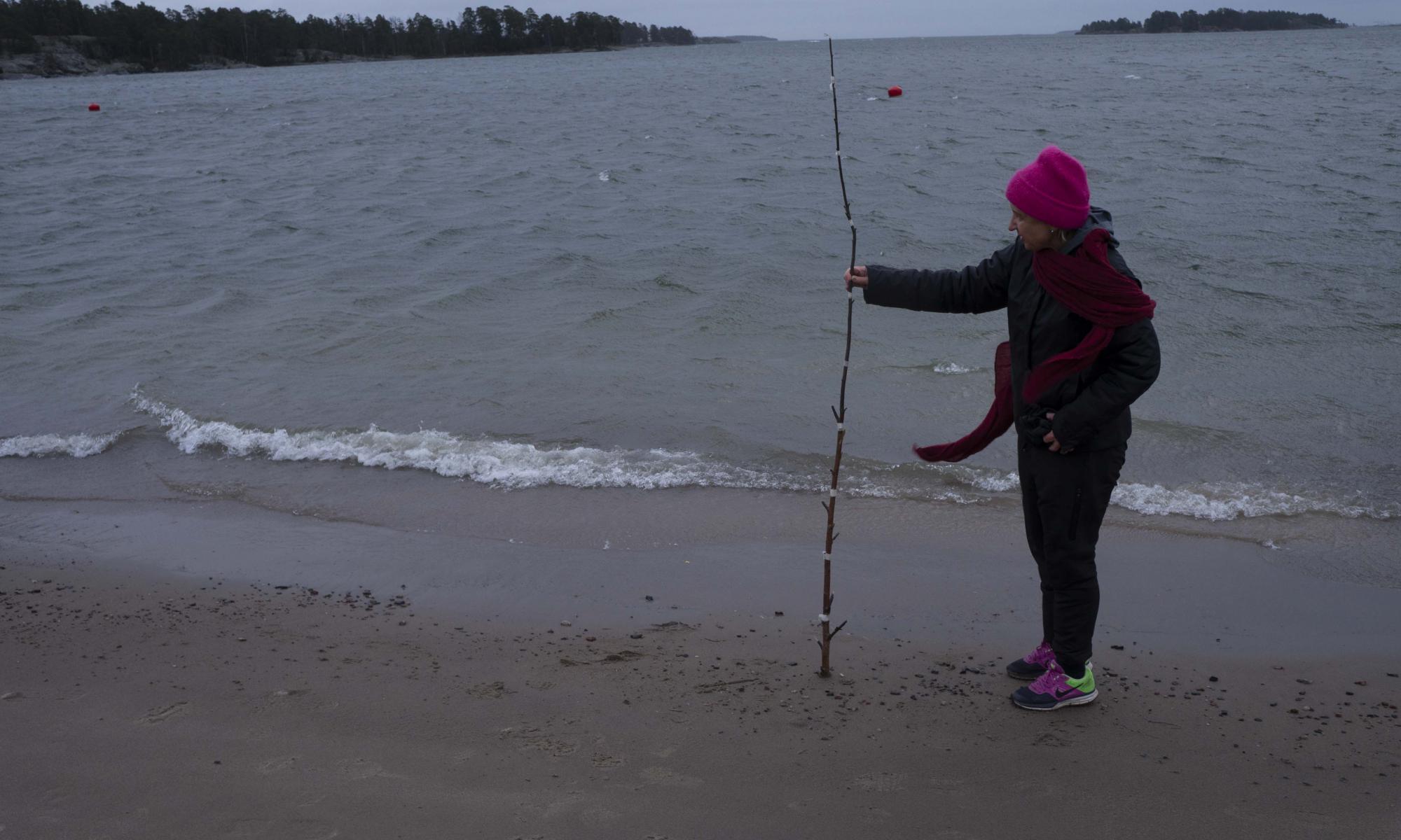 Marjatta Oja mittaa merenpinnan korkeutta rannalla.