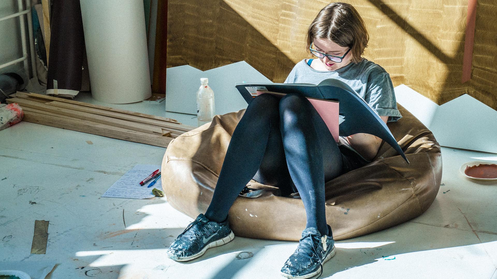 Taideyliopiston opiskelija istuu lukemassa. Kuva: Veikko Kähkönen