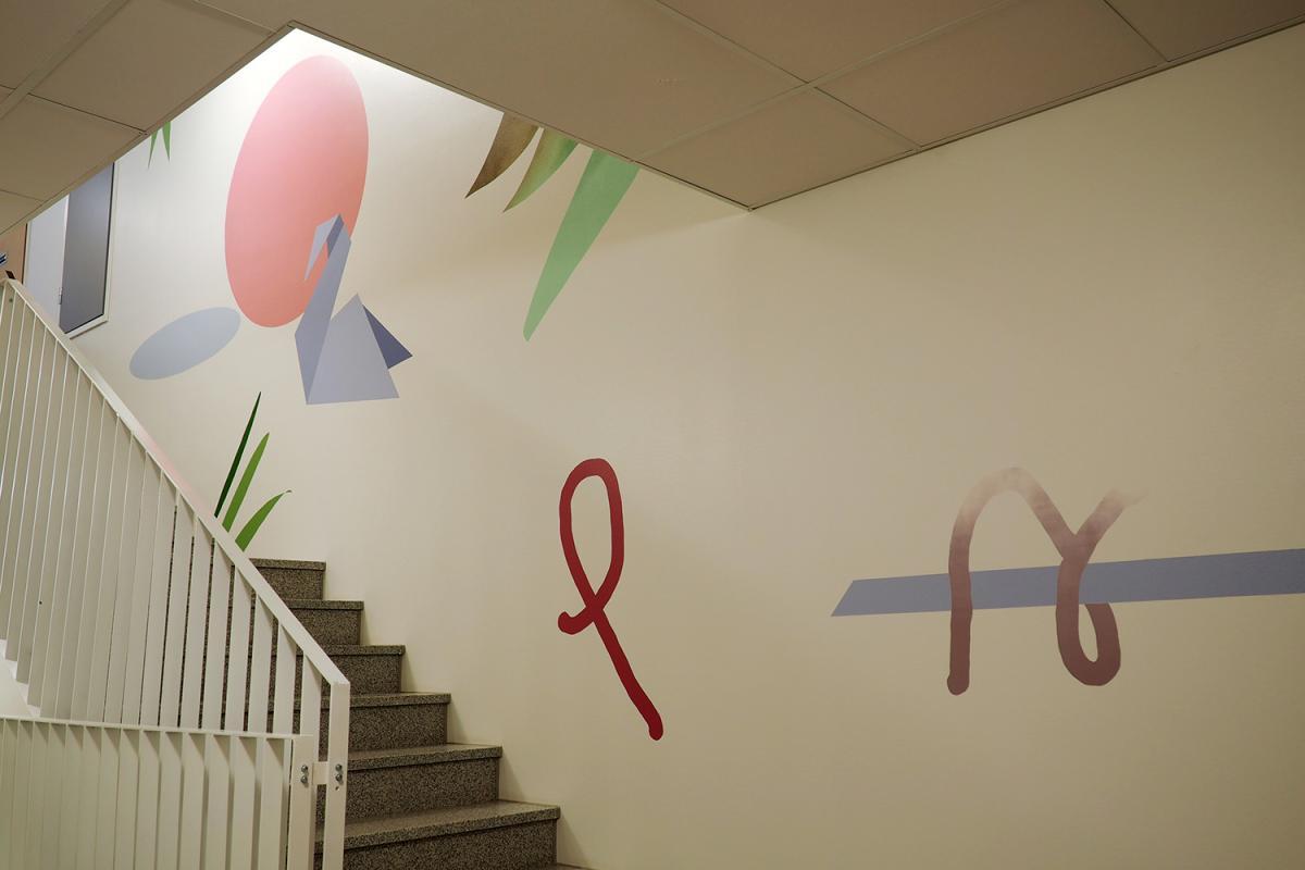 Kuva on rappukäytävästä. Seinällä on Katarina Maisterin maalaus, joka sisältää erilaisia muotoja.