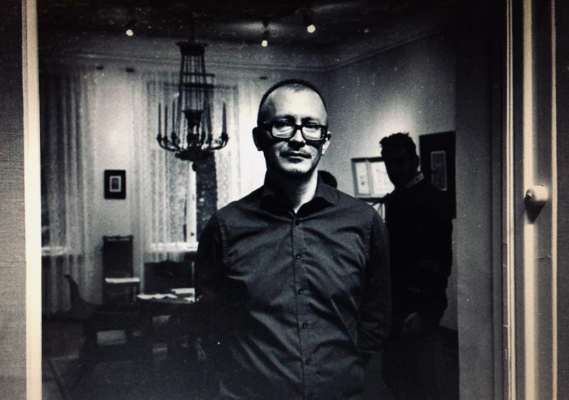 Ilya Orlov katsoo kameraan mustavalkoisessa kuvassa. Kuvan taustalla on huone, jossa ihmisiä ja suuri kynttiläkruunu katossa.