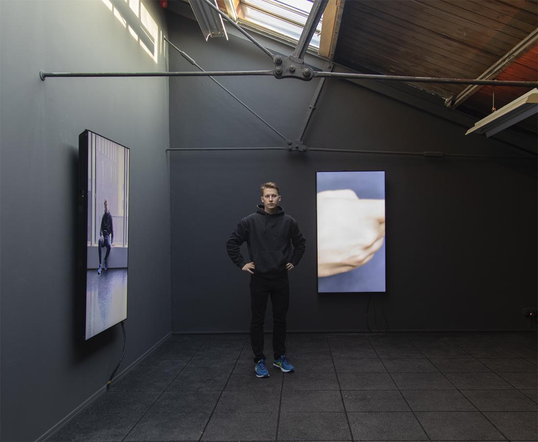 Taiteilija seinoo työhuoneessaan teostensa ympäröimänä.