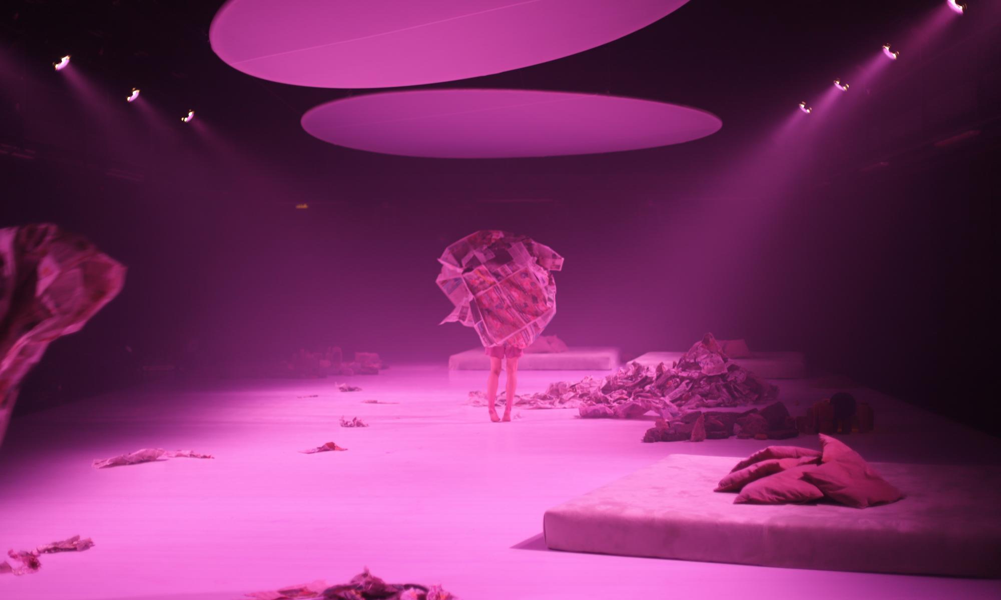Syvä näyttämö, jonka pinkissä valossa esiintyjä seisoo valtavassa sanomalehtipallossa ja vain jalat näkyvät.