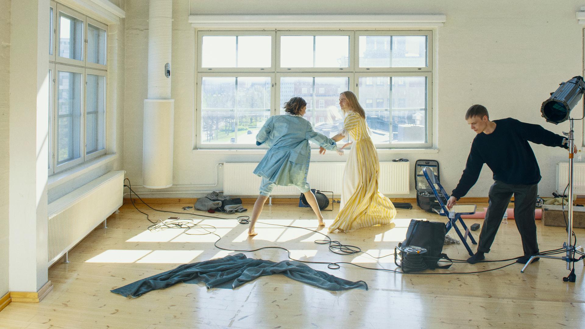 Kaksi henkilöä esiintymisasuissa liikkuvat valoisassa harjoitussalissa. Etualalla lattialla on ruttuinen kangas ja johtoja. Reunalla kolmas henkilö, joka pitää kiinni kuvausvalon rungosta ja johdoista.