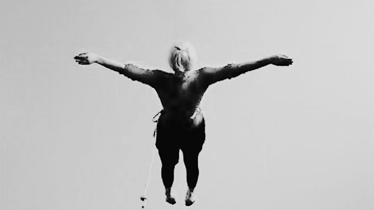 Henkilö lhyppää kädet levällään, taustalla taivasta. Kuva on mustavalkoinen.