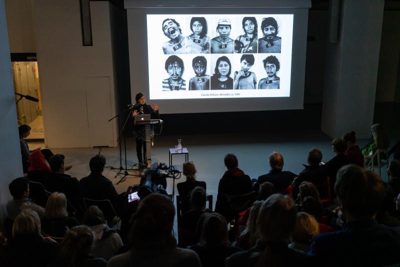 Andre Giunta luennoi yleisön edessä. Puhujan takana on heijastettu valokuvateos, jossa on ihmisiä.