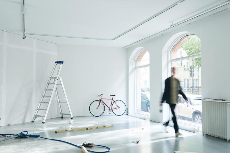 Project Room gallery from the inside, person walking in front of a window, a bike and a ladder in the background.