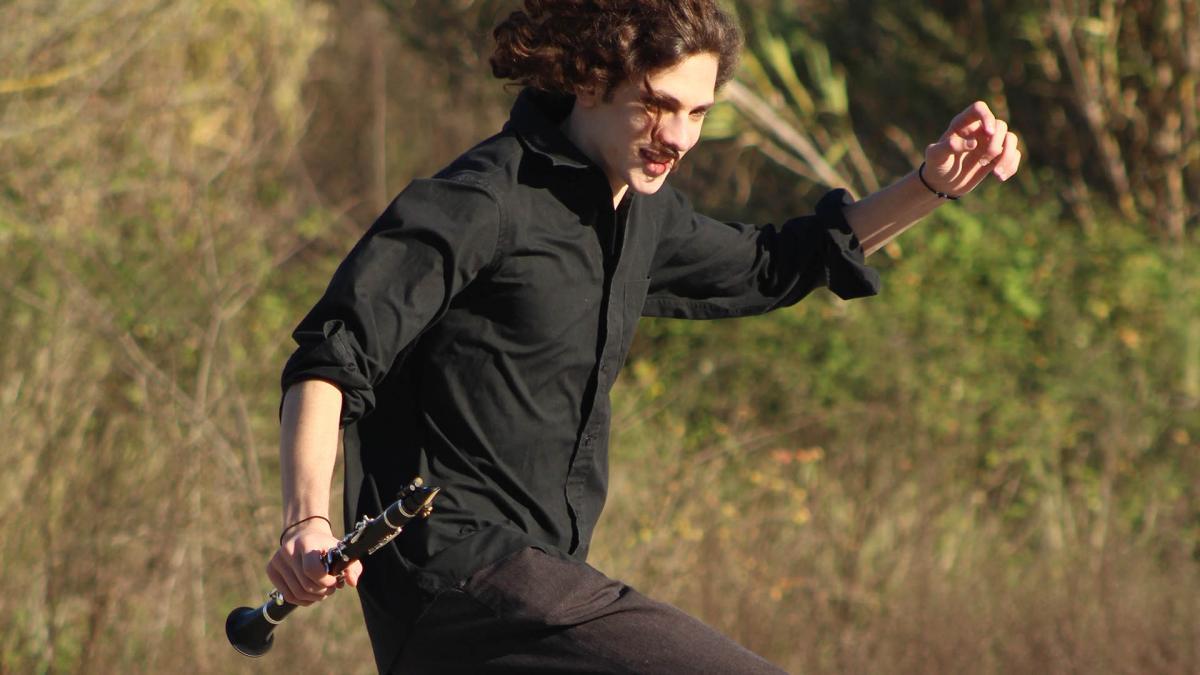 Nuori mies juokseen pellolla instrumentin kanssa