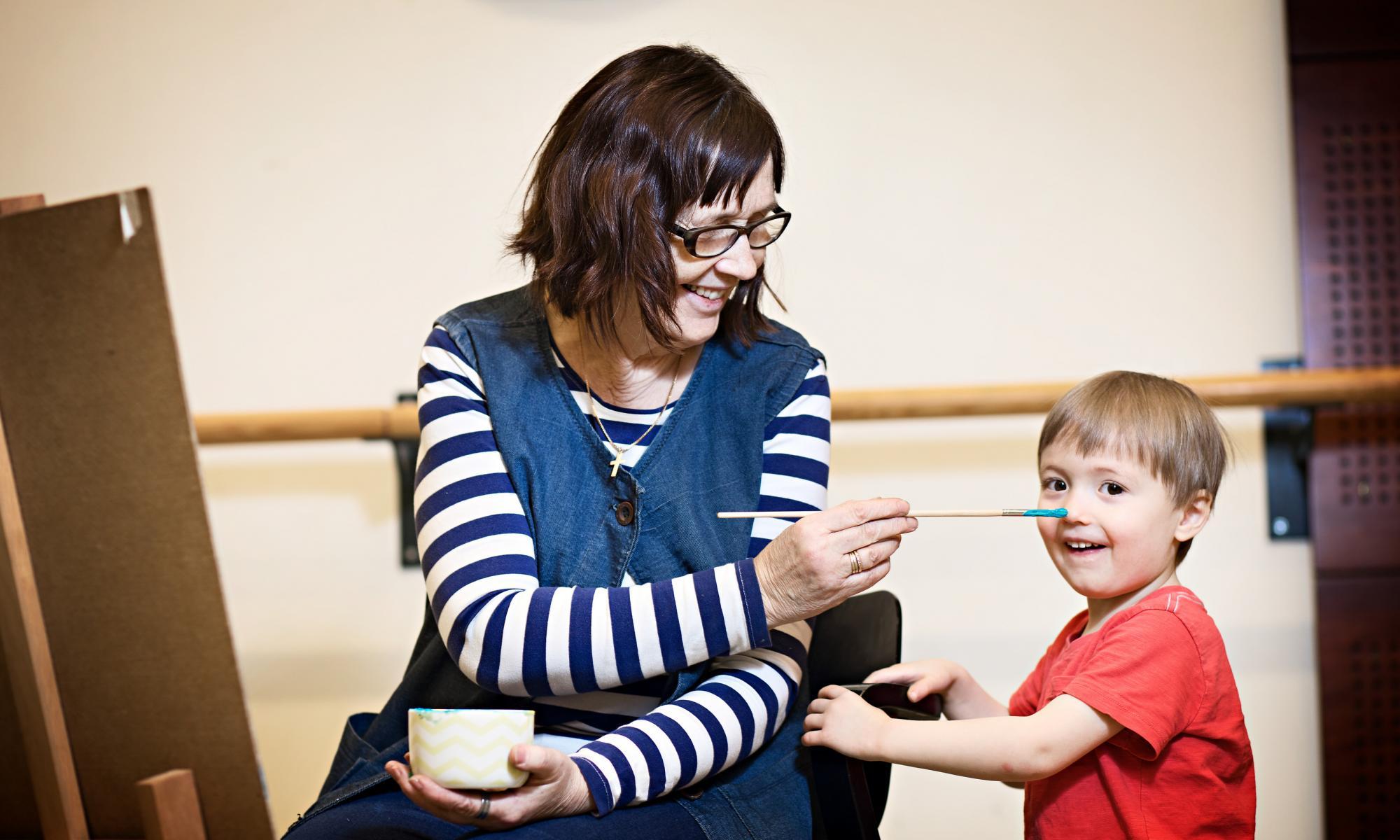 Istuva aikuinen sipaisee maalisiveltimellä pienen lapsen nenää. Molemmat hymyilevät.