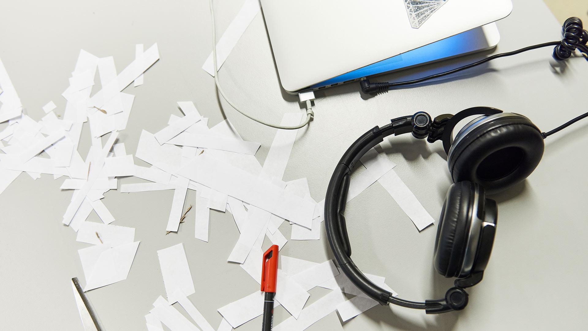 Kuulokkeet, paperinpaloja ja tietokone pöydällä