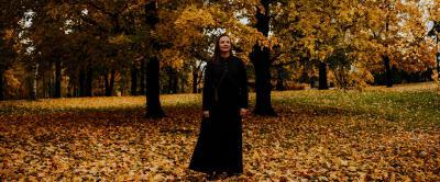 Taru Hämäläinen poseeraa syksyisessä puistossa tummiin pukeutuneena.