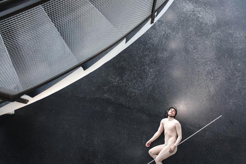 A man in a leotard, helmet and a metal stick on a stone floor photographed from the air above him.