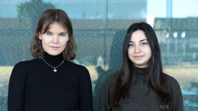 Kaksi naista seisoo vierekkäin lasiseinän edessä ja katsoo suoraan kameraan.