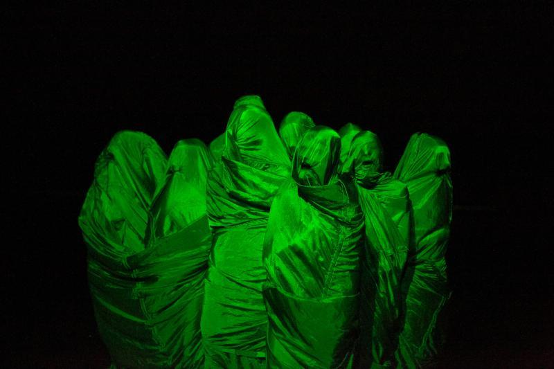 Esiintyjiä vihreän kankaan alla, hengittämässä kangasta sisään niin että heidän kehonsa muodot piirtyvät esiin kankaassa.