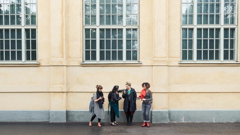 Fyra människor skrattar framför Teaterhögskolan.