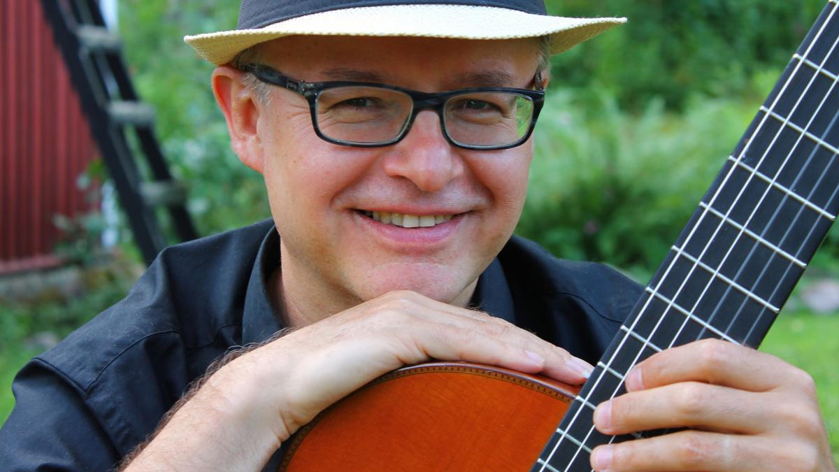 Andrzej Wilkus sits on a guitar and smiles at the camera.