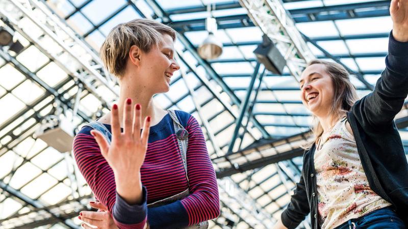Kaksi naista juttelee iloisesti, takana näkyy lasinen katto.